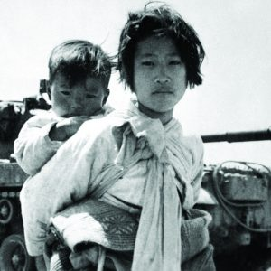 War weary Korean girl with brother on her back in front of a tank. 1951.