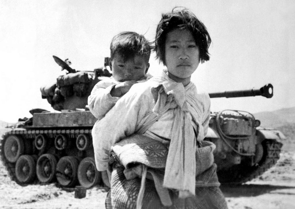 War weary Korean girl with brother on her back in front of a tank.