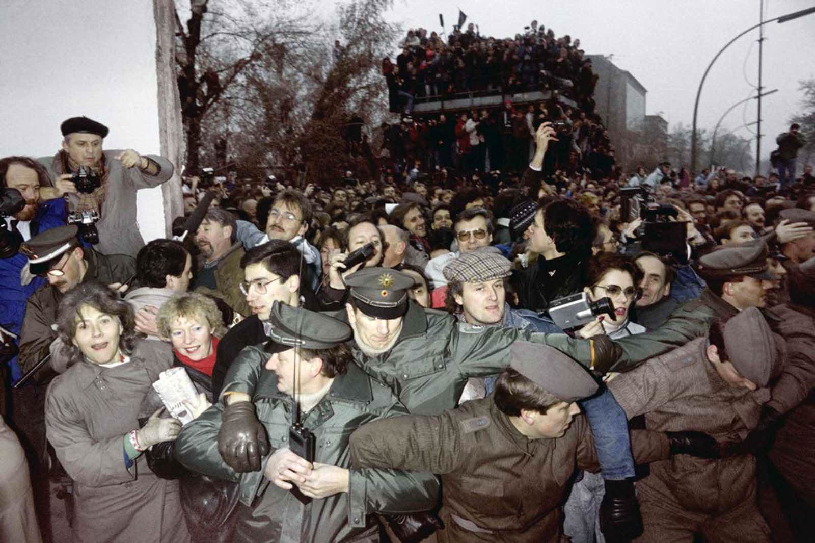East and West German Police try to contain the crowd of East Berliners flowing through the recent opening made in the Berlin wall at Potsdamer Square, on November 12, 1989.