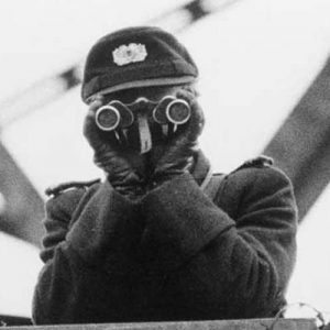 East German VOPO, a quasi-military border policeman using binoculars, standing guard on one of the bridges linking East and West Berlin, in 1961.