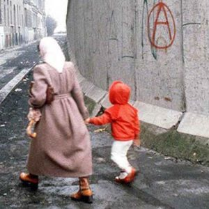A woman and child walk beside a section of the Berlin Wall.