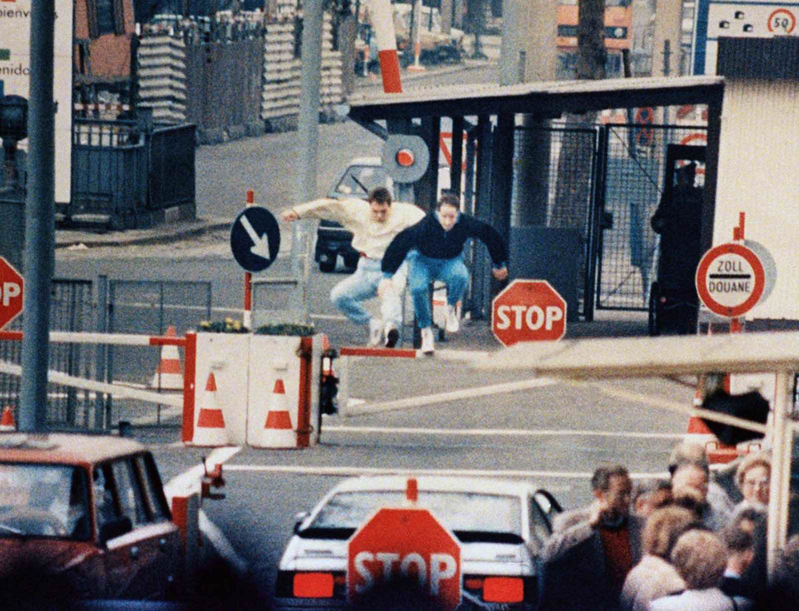 Two East Berliners jump across border barriers on the Eastern side of border checkpoint at Chaussee Street in Berlin in April of 1989. They were stopped by gun wielding East German border guards and arrested while trying to escape into West Berlin. People in the foreground, still in East Berlin, wait for permits to visit the West.
