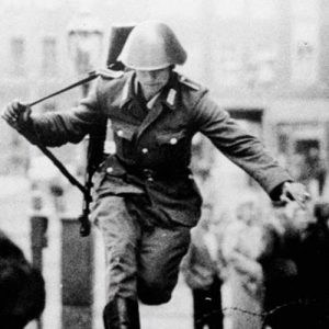 """Conrad Schumann was immortalized in this photograph as he leapt across the barricade that would become the Berlin Wall. The photo was called """"The Leap into Freedom"""". It became an iconic image of the Cold War."""