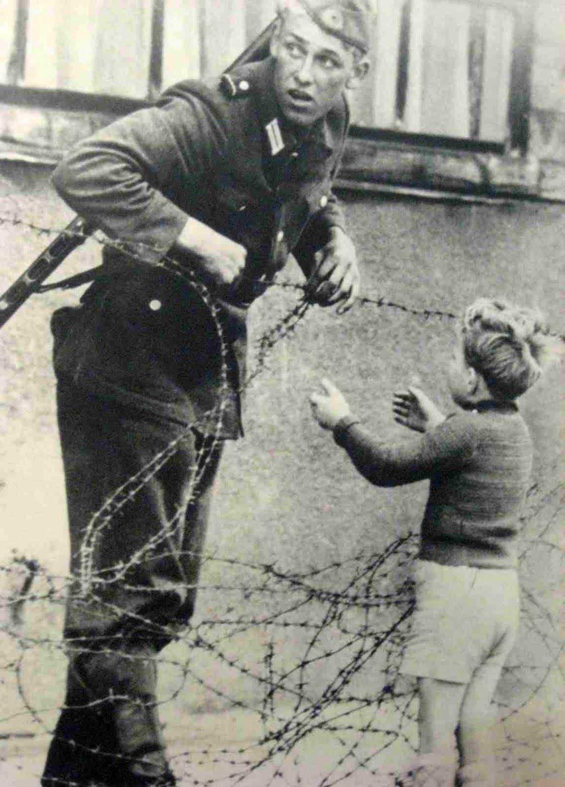 East German soldier helps a little boy sneak across the Berlin Wall, August 13, 1961.