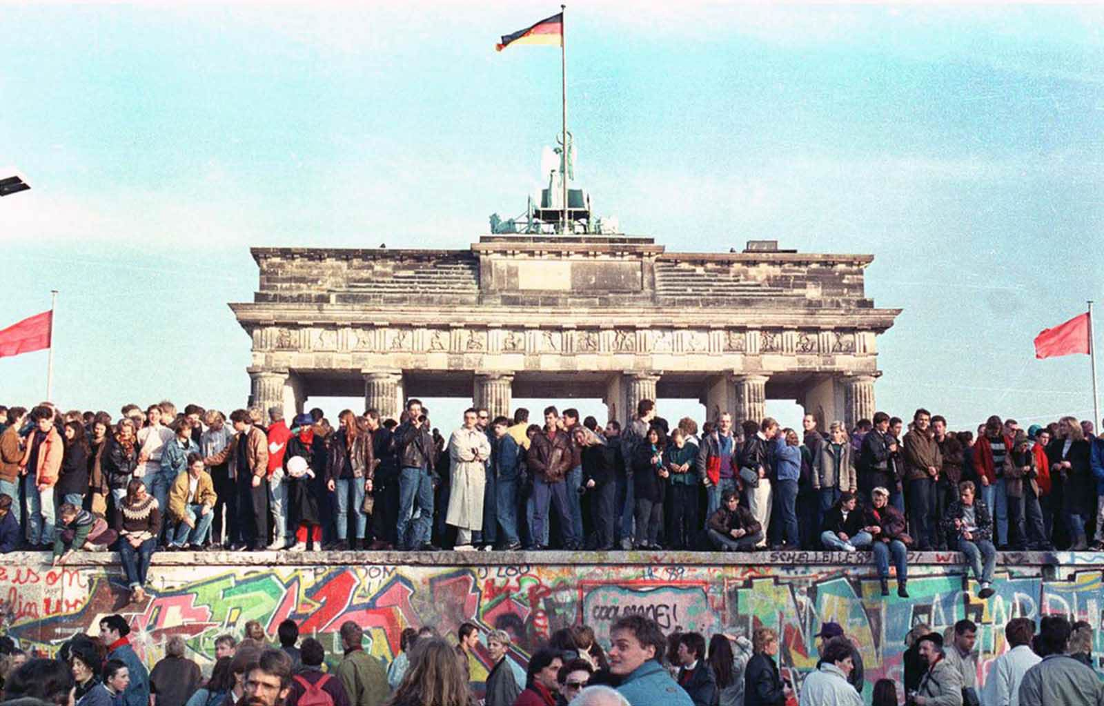 West Berlin citizens hold a vigil atop the Berlin Wall in front of the Brandenburg Gate on November 10, 1989, the day after the East German government opened the border between East and West Berlin.