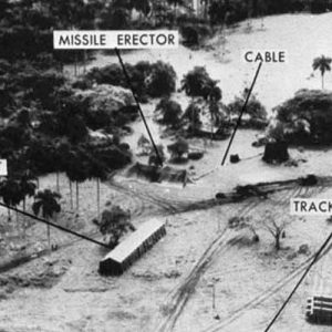 Evidence presented by the U.S. Department of Defense, of Soviet missiles in Cuba. This low level photo, made October 23, 1962, of the medium range ballistic missile site under construction at Cuba's San Cristobal area. A line of oxidizer trailers is at center. Added since October 14, the site was earlier photographed, are fuel trailers, a missile shelter tent, and equipment. The missile erector now lies under canvas cover. Evident also are extensive vehicle tracks and the construction of cable lines to control areas.