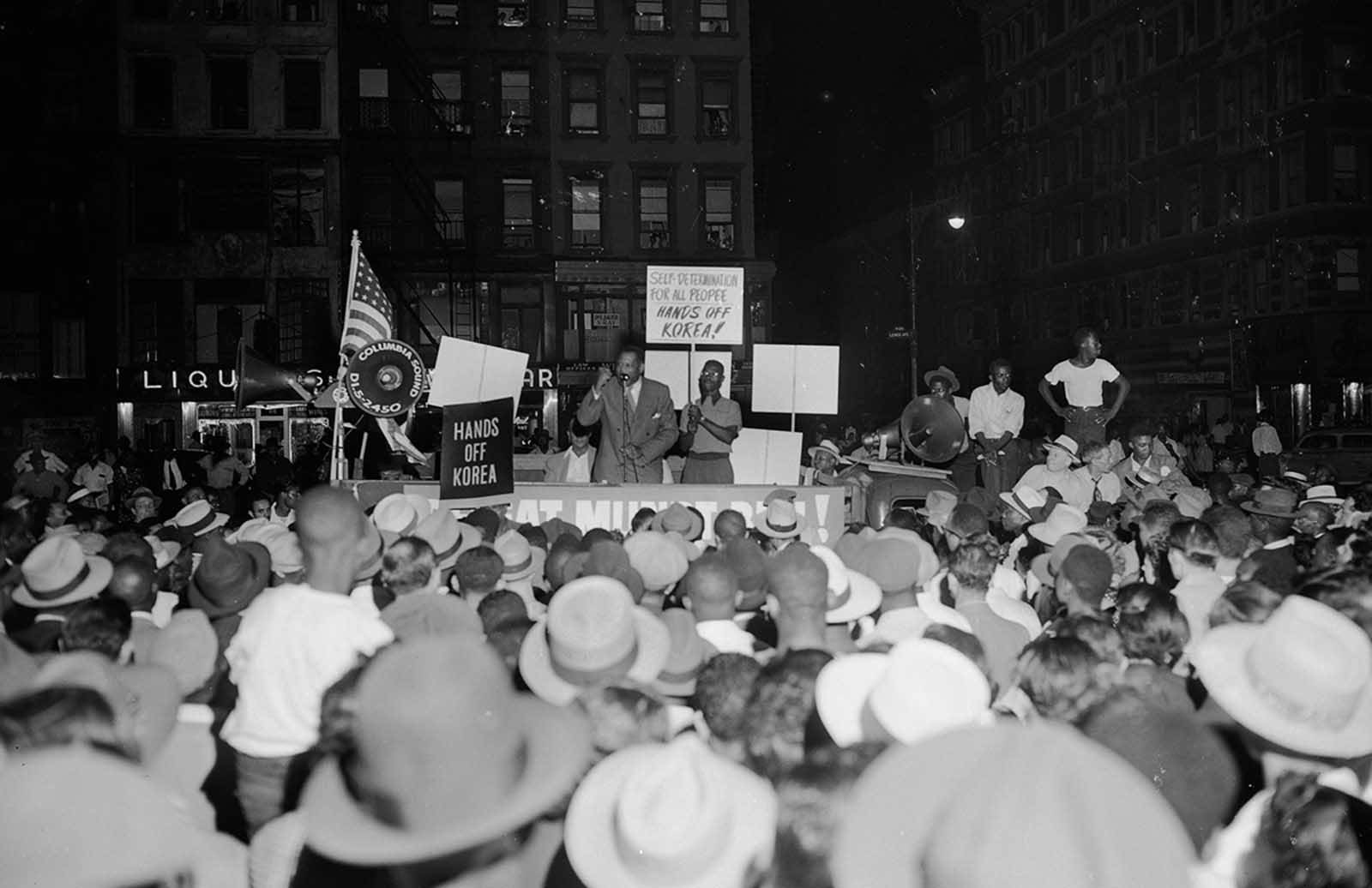 """Singer Paul Robeson addresses a """"Hands Off Korea"""" rally from a sound truck at the corner of 126th Street and Lenox Avenue in the Harlem section of New York, on July 3, 1950."""