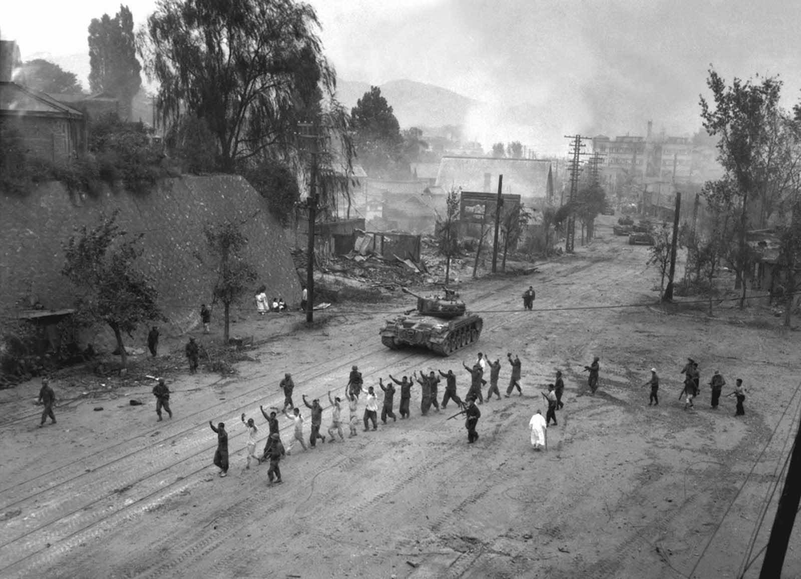 A U.S. Marine tank follows a line of prisoners of war down a village street. September 26, 1950.