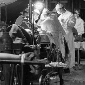 A mobile army surgical hospital somewhere in Korea on October 26, 1951. The patient in the left foreground is receiving blood plasma, while behind him two operations are taking place, one at left and one in the center. Photographer Healy took the photos as he found them. Everyone was so busy that no one had time to pose.