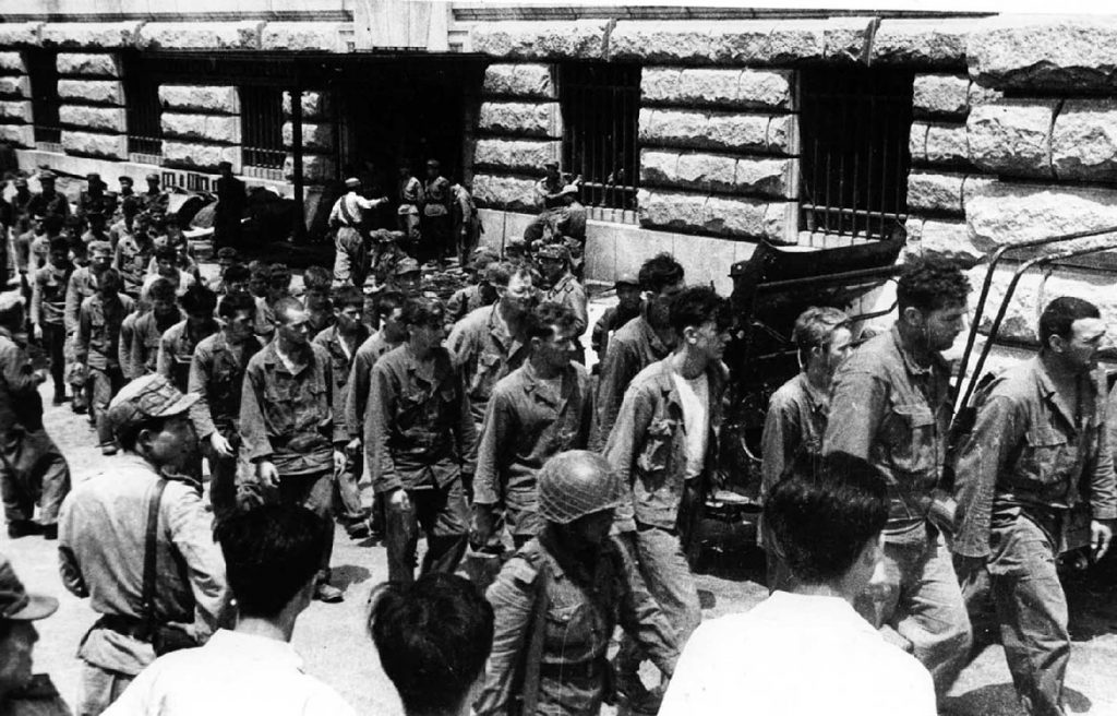 In this undated photo from North Korea's official Korean Central News Agency, American combatants captured during the Korean War march down a street.