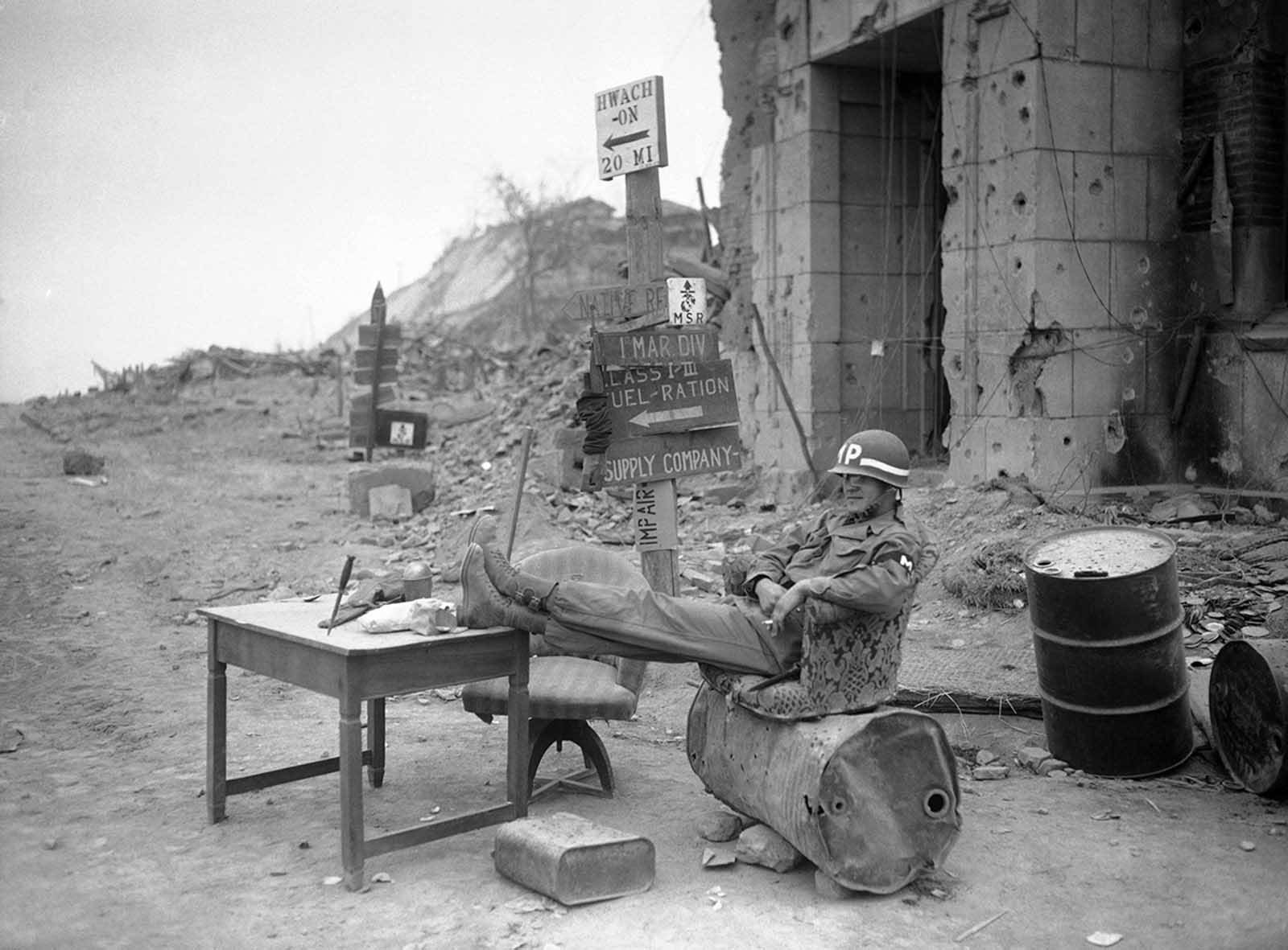 """All Sgt. Bernard Young lacks is a private secretary to complete his """"office"""" setting, on May 3, 1951. The Detroit, Michigan, military policeman takes his ease in almost deserted Chunchon, South Korea after the bulk of UN forces had withdrawn southward. Only an infantry rear guard unit remained between him and the advancing Communists."""