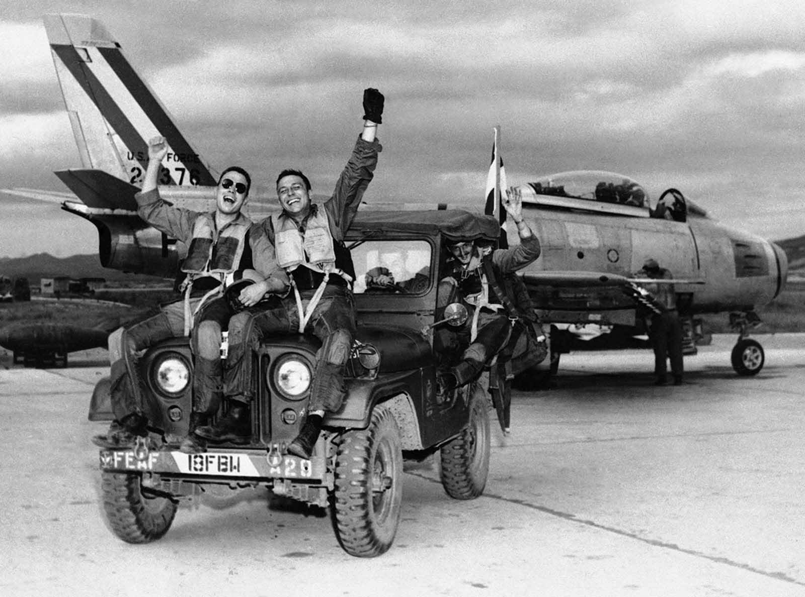 Three happy fliers of the 18th Fighter Bomber wing let the world know how they feels as they returned from a combat mission over North Korea to learn of the armistice signing on July 29, 1953. Left to right are: 2nd Lt. John Putty, Dallas, Tex.; 1st Lt. James A. Boucek, Ottawa, Kansas,: and 1st Lt. Richard D. Westcott, Houston, Tex., waving from the back seat of the jeep.