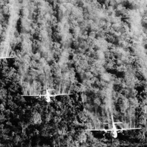 """Four """"Ranch Hand"""" C-123 aircraft spray liquid defoliant on a suspected Viet Cong position in South Vietnam in September of 1965. The four specially equipped planes covered a 1,000-foot-wide swath in each pass over the dense vegetation."""